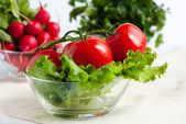 Tomatoes on the background of radish and parsley — Stock Photo