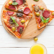 Mouthwatering pizza with salami, cut into slices, top view - Stock Photo