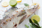 Large raw fish and spices on a wooden surface — Stock Photo