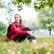 Pretty girl sitting on the autumn leaves — Stock Photo