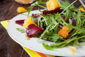 Beet salad with arugula and slices of orange — Stock Photo