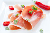 Ham with hot pepper and oregano leaves — Stock Photo