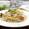 Spaghetti with grated Parmesan and basil - Stock Photo
