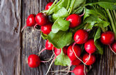 Large bunch of fresh radish on dark boards — Stock Photo