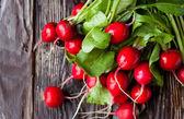 Large bunch of fresh radish on dark boards — Stock Photo