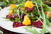 Beet salad with fresh arugula and slices of orange — Stock Photo