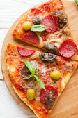 Two large slices of pizza with cheese, mushrooms and salami on b — Stock Photo
