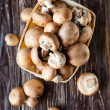 Fresh champignons in a basket on dark boards - Stock Photo