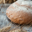 Round loaf grain bread and wheat ears - Stock Photo