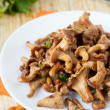 Stock Photo: Roasted chanterelle mushrooms on a white plate