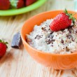Oatmeal with milk and strawberries - Stock Photo