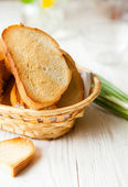 Toasted bread in the bread basket on white boards — Stock Photo