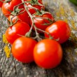 Stock Photo: Branch of cherry tomatoes on the board