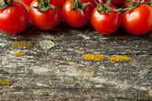 Wooden background with cherry tomatoes — Stock Photo