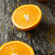 Halves of orange on very old boards - Stock Photo