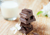 Chunks of dark chocolate in a glass of milk on the boards — Stock Photo