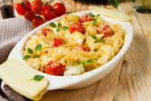 Penne under the grated cheese with cherry tomatoes — Stock Photo