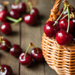 Ripe cherries in wicker basket basket — Stock Photo #26227521