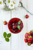 Strawberry jam in a bowl on a white table, top view — Stock Photo