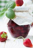 Jahodový jam ve sklenici na stůl bílý — Stock fotografie