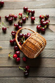 Cherries in bulk on a table and a basket — Stock Photo
