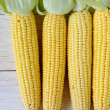 Fresh corn cob on a wooden surface — Stock Photo