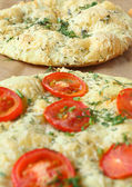 Italian focaccia (pizza) with tomatoes and herbs — Stock Photo