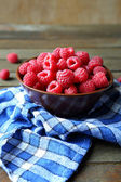 Fresh and ripe raspberries in a bowl on a wooden table — Stock Photo
