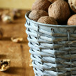 Fresh walnuts in a wicker bucket and peel — Stock Photo