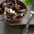 Fried wild mushrooms with garlic in a ceramic bowl — Stock Photo