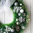 Christmas wreath in silver on white door — Stock Photo