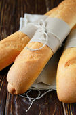 Crunchy and flavorful baguettes on the wooden table — Stock Photo