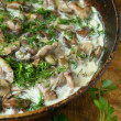 Fried mushrooms in a cream sauce with herbs — Stock Photo