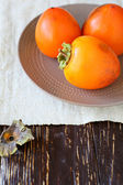 Juicy ripe persimmon on a plate — Stock Photo