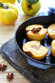 Baked yellow quince on an old skillet — Stock Photo