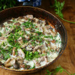 Wild mushrooms stewed in sour cream in a pan — Stock Photo