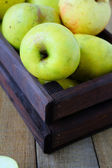 Green apples in a wooden crate — Stock Photo