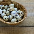 Raw quail eggs in a basket — Stock Photo