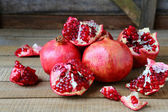 Ripe pomegranates on a rustic table — Stock Photo