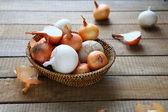 Cebollas en una canasta de mimbre — Foto de Stock
