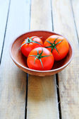 Three ripe red tomatoes in a bowl — Stock Photo
