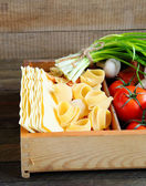 Uncooked pasta in wooden box — Stock Photo