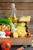 Pasta and ingredients on wooden background — Stock Photo