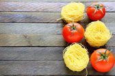 Uncooked pasta and fresh tomatoes — Stock Photo