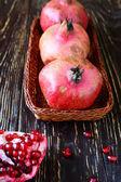 Three pomegranate on a wicker tray — Stock Photo