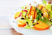 Appetizing salad with persimmons — Stock Photo