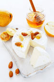 Cheese, nuts and honey on the board — Stock Photo