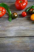 Tomates mûres sur des planches en bois, fond — Photo