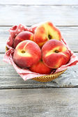 Fragrant peaches in a wicker basket, — Stock Photo