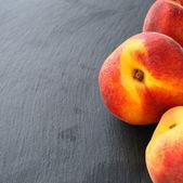 灰色の背景上の新鮮な桃 — ストック写真